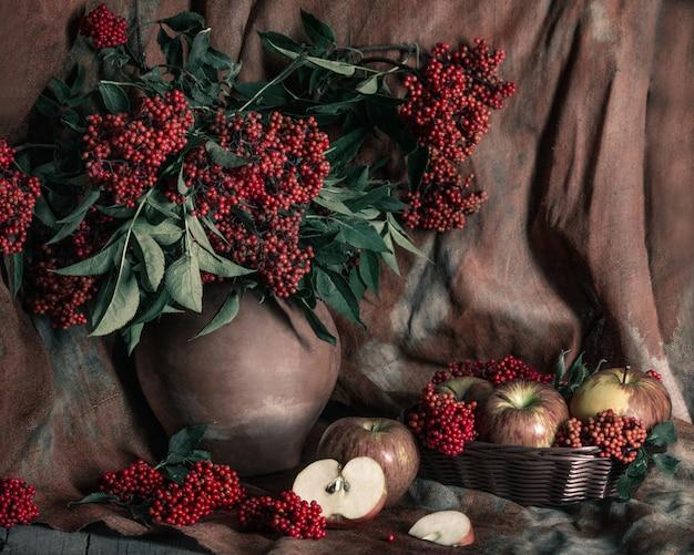 Sambuco rosso brillante nel vecchio vaso di argilla e mele sul tavolo con il vecchio sfondo di tessili. natura morta in stile vintage