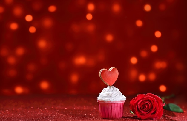 Cuore rosso brillante sulla parte superiore del muffin per san valentino con fiore di rosa come una dolce dichiarazione d'amore. copia spazio