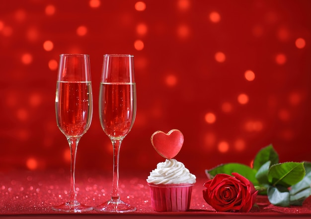 Cuore rosso brillante sulla focaccina per san valentino con fiori di rosa e due bicchieri di champagne. copia spazio