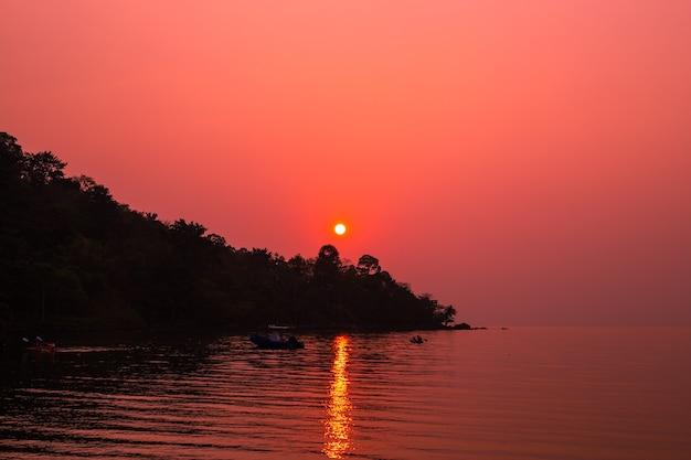 Tramonto rosso brillante in riva al mare su un'isola tropicale in asia