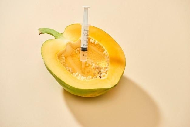 Frutto di papaia matura brillante con siringa che estrae liquido e mostra il concetto di trattamento della cellulite