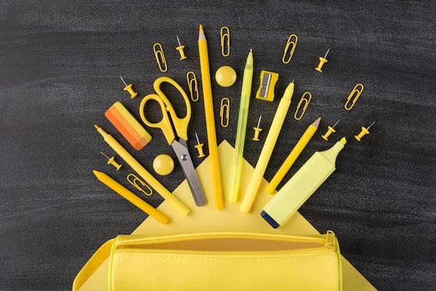 Cancelleria luminosa della scuola che cade dal concetto della scatola di matita. in alto sopra la foto vista dall'alto del set di cancelleria gialla disposta in caduta e astuccio isolato sulla lavagna