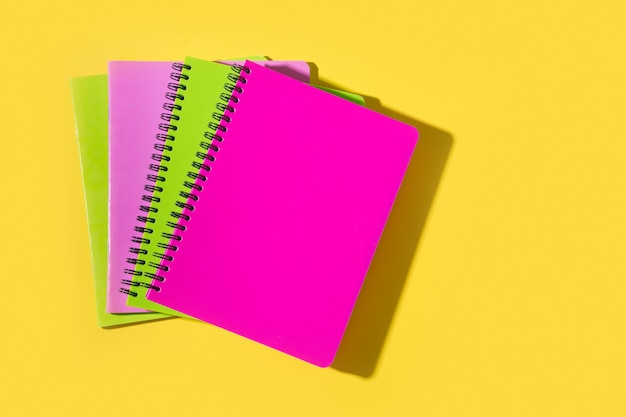 Materiale scolastico luminoso, quaderni su giallo. vista dall'alto, piatto.