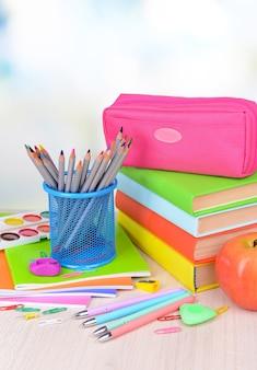 Materiale scolastico luminoso sul tavolo su sfondo chiaro