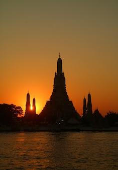 Il luminoso raggio di sole al tramonto che splende attraverso la sagoma del tempio dell'alba o wat arun, il punto di riferimento più noto della thailandia