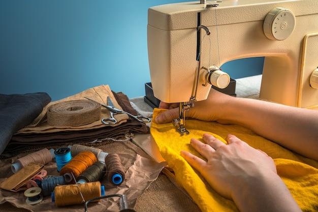 Sfondo di cucito luminoso con mani di donne, tessuto giallo, filo e macchina da cucire su sfondo blu. vista laterale con copia spazio.