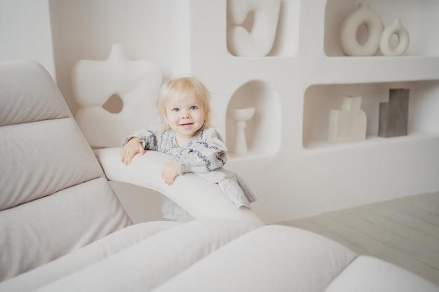 Luminoso ed elegante appartamento interno ritratto di famiglia piccola figlia ragazza bionda in eleganti abiti beige, giocando a giochi divertenti a casa sorridendo
