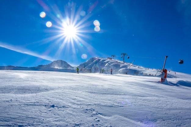 Tempo soleggiato luminoso sulla pista da sci. skilift e molti sciatori
