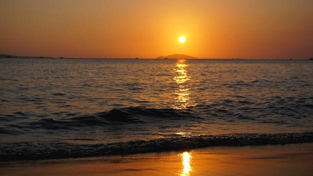 Tramonto luminoso con il sole giallo sotto la superficie del mare - vacanze estive e concetto di avventura di viaggio nella natura.