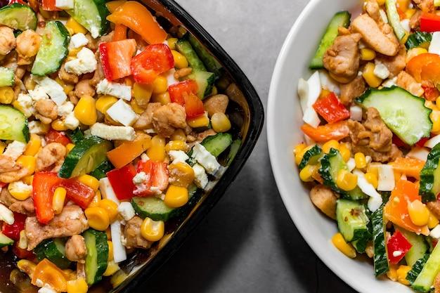 Insalata di verdure brillante con pollo su uno sfondo di cemento grigio. preparare una deliziosa insalata per una dieta sana. due ciotole di insalata di verdure con primo piano di pollo