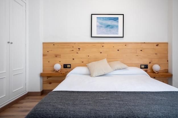 Interno bianco luminoso della camera da letto decorato con una foto delle onde del mare e una testiera in legno