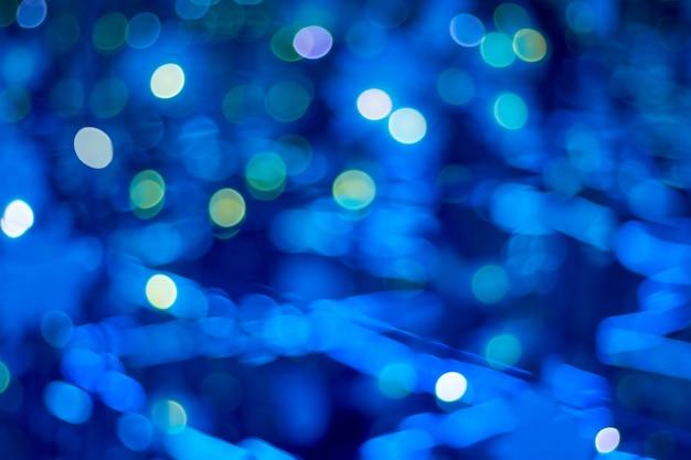 Le luci sfocate bianche brillano e brillano su uno sfondo scuro