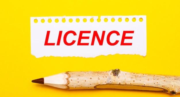 Su uno sfondo giallo brillante, una grande matita di legno e un foglio di carta strappata con il testo license