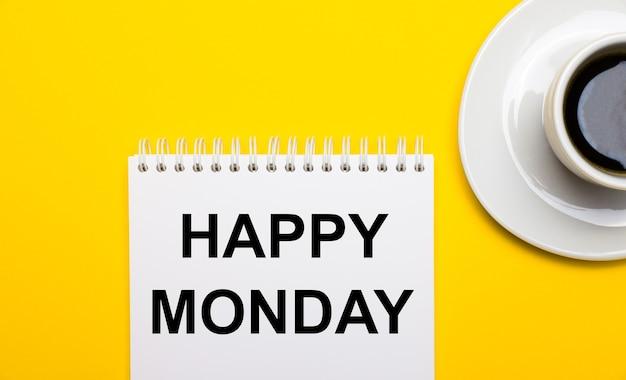 Su uno sfondo giallo brillante, una tazza bianca con caffè e un blocco note bianco con le parole happy monday