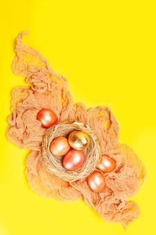 Fondo giallo luminoso di festa di pasqua con le uova colorate rosa e dorate