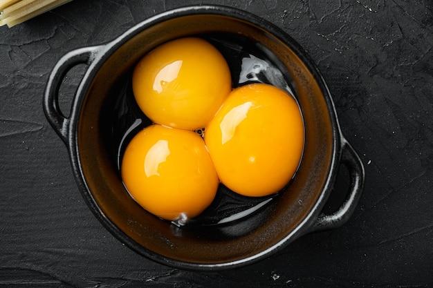 Set di tuorli d'uovo giallo brillante, su sfondo di pietra nera, vista dall'alto piatta