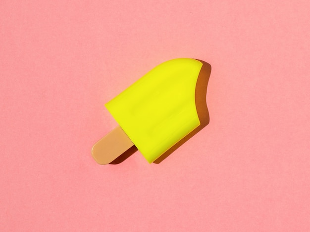 Gelato giallo brillante in piena luce su uno sfondo rosa.