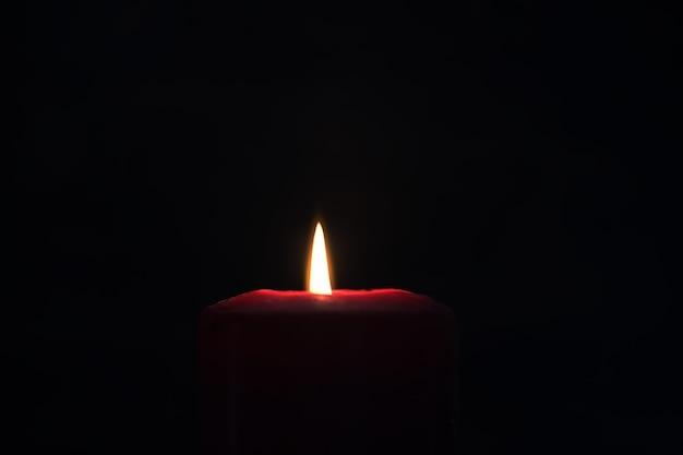 Luce gialla brillante di una fiamma di candela che brucia nel buio