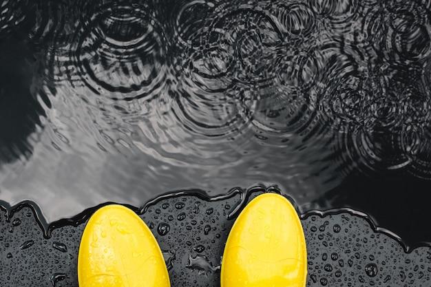Stivali di gomma gialli brillanti stanno sotto la pioggia sul nero