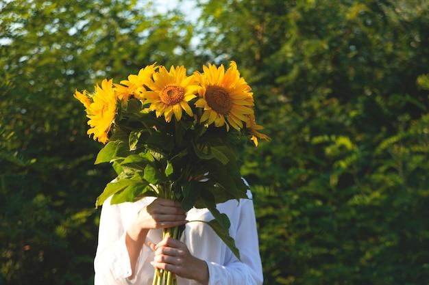 Girasole giallo brillante nelle mani di una donna che vuole essere più vicina alla natura estiva