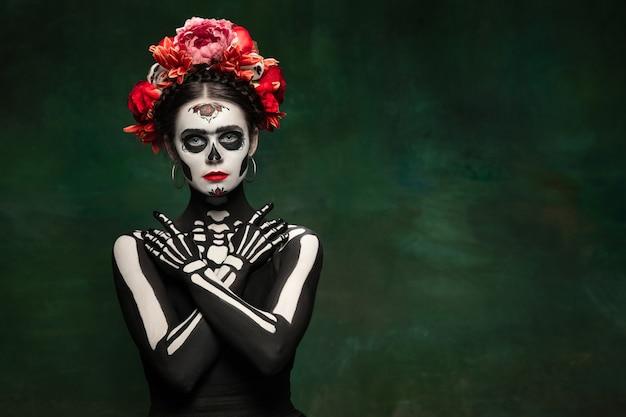 Luminoso. ragazza giovane come la morte di santa muerte saint o il teschio di zucchero con trucco luminoso. ritratto isolato su sfondo studio verde scuro con copyspace. festeggiando halloween o il giorno dei morti.