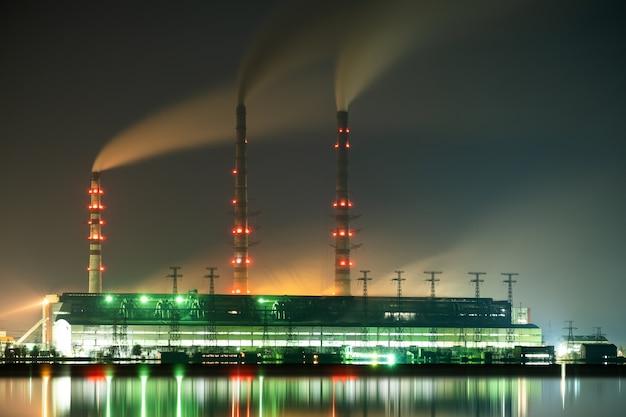 Tubi alti della centrale elettrica a carbone luminosamente illuminati con fumo nero che si muove verso l'alto inquinante atmosfera di notte con riflessi nell'acqua del lago.