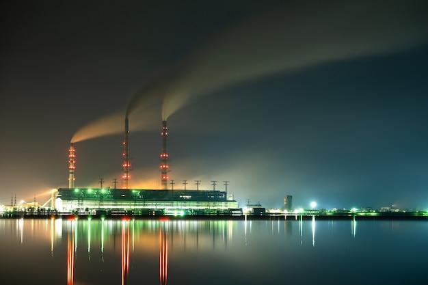 Centrale elettrica a carbone brillantemente illuminata con tubi alti con fumo nero.