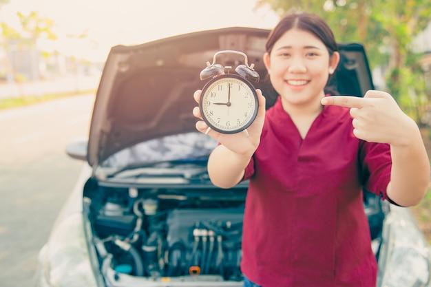 Portare l'auto al servizio in base al concetto di pianificazione degli orari, sorriso felice della donna con sveglia e sfondo del cofano aperto dell'auto.