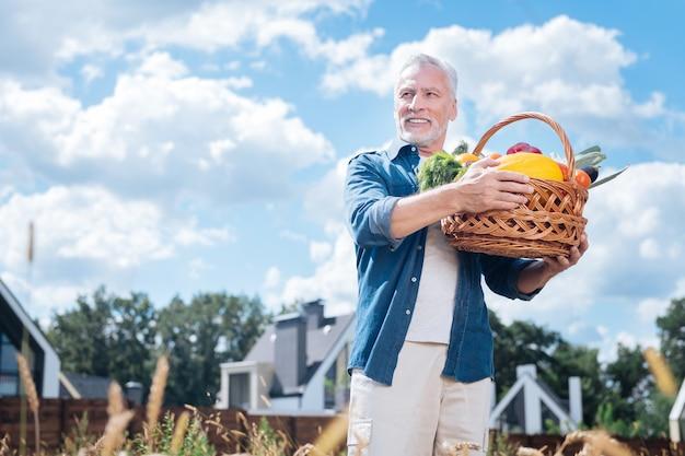 Portare le verdure. uomo barbuto maturo che si sente eccitato e conteso mentre porta a casa un grande cesto con verdure fresche