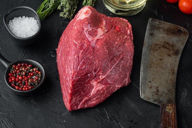 Set crudo di carne di manzo di petto con il vecchio coltello da macellaio, su sfondo nero