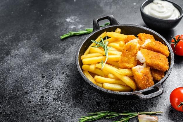 Pesce e patate fritte britannico sulla tavola nera.