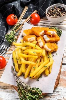 Pesce e patate fritte britannico sulla tavola di legno bianca.