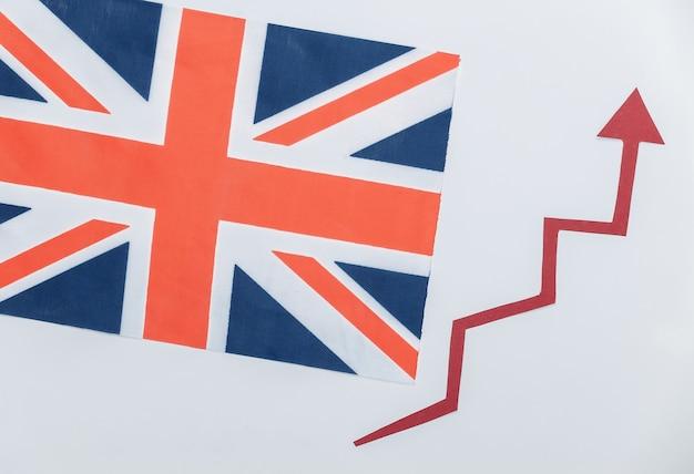 Bandiera britannica con freccia di crescita rossa. grafico a freccia che sale. la crescita economica