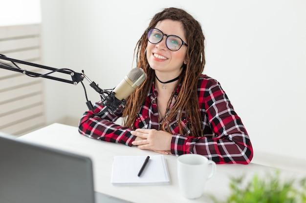 Trasmissione di musica dj e persone concetto donna con i dreadlocks e gli occhiali che lavorano alla radio