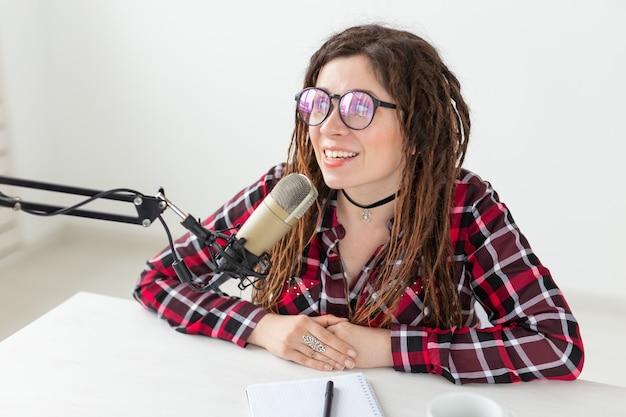 Trasmissione, musica, dj e concetto di persone - donna con dreadlocks e occhiali che lavorano alla radio.