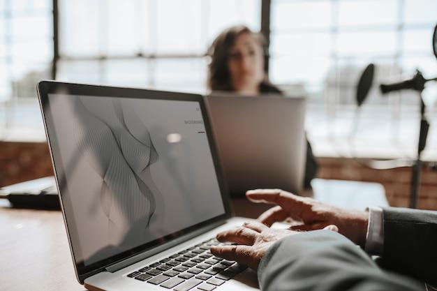 Emittente in uno studio che utilizza un mockup di schermo per laptop
