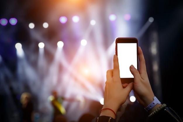 Trasmissione di uno spettacolo musicale su internet tramite un telefono cellulare. schermo vuoto dello smartphone bianco
