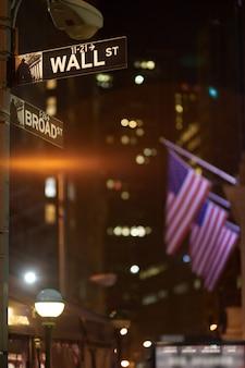 Broadway e wall street segni di notte con noi bandiere sullo sfondo, manhattan, new york