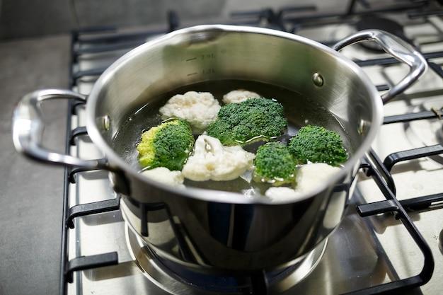 Broccoli e cavolfiori bolliti in una casseruola grigia su un fornello a gas