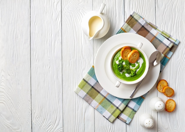 Zuppa di broccoli in una ciotola di zuppa bianca servita con fette di baguette tostate e panna fresca, vista dall'alto, flatlay, spazio di copia