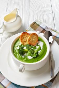 Zuppa di broccoli con menta fresca in una ciotola di zuppa bianca servita con fette di baguette tostate e panna fresca, vista verticale dall'alto