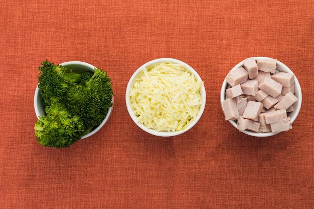 Broccoli, petto di tacchino a dadini e formaggio grattugiato in pentole bianche su un tavolo con una tovaglia rossa. messa a fuoco selettiva. vista dall'alto.