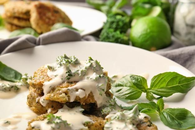 Frittelle di broccoli servite con salsa, prezzemolo e foglie di basilico su piatto bianco
