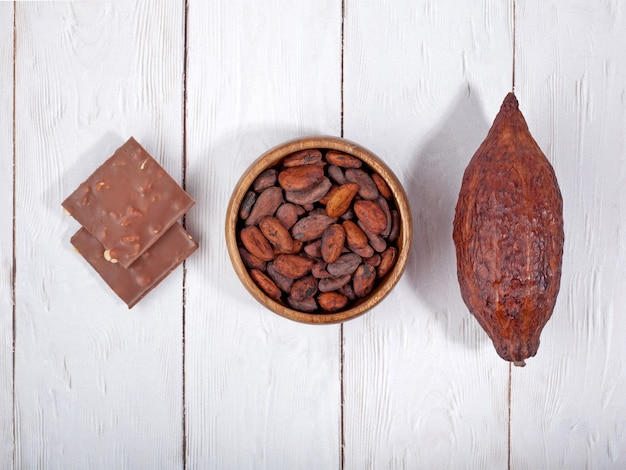 Barra rotta di cioccolato al latte baccello di cacao e fave di cacao su sfondo di legno chiaro vista dall'alto