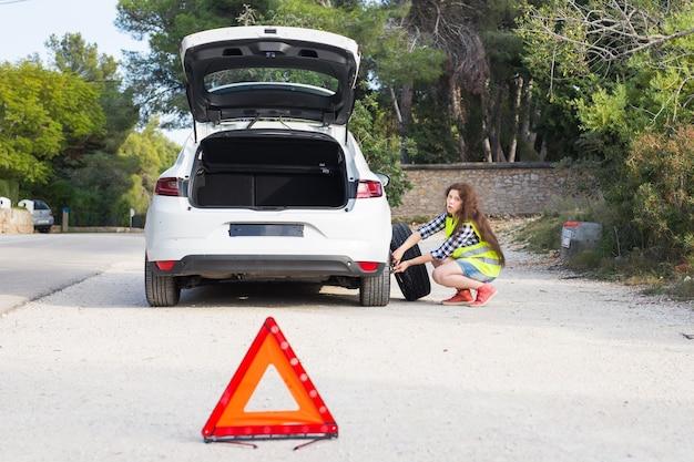 Un'auto rotta, un segno di incidente e una donna capisce qual è il problema