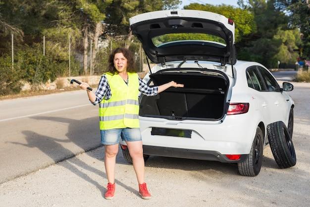 Un'auto rotta. la giovane donna non sa come cambiare la ruota
