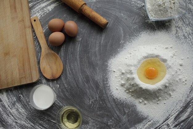 Uovo di gallina rotto in un mucchio di farina, olio d'oliva, latte, utensile da cucina, tavolo grigio
