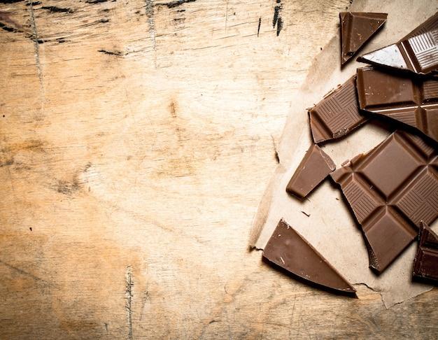 Barra di cioccolato rotta su uno sfondo di legno