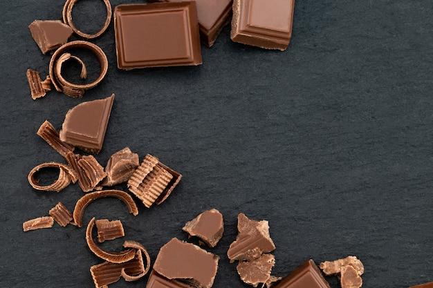 Pezzi di cioccolato rotti e scaglie di cioccolato su uno sfondo scuro. vista dall'alto con copyspace per il tuo testo.