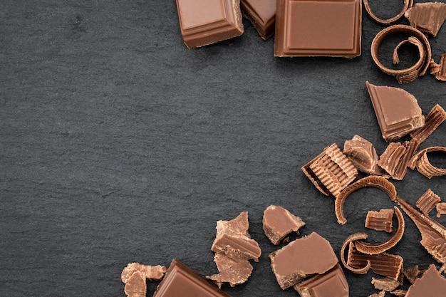 Pezzi di cioccolato rotti e scaglie di cioccolato su uno sfondo scuro.